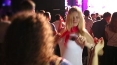 Two happy women dance among many people in night club Stock Footage