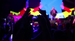 Hands hold phone, that shoots video during performance in night club Stock Footage
