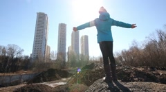 Back of girl with arms outstretched, sun and tall buildings - stock footage