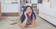 Happy woman at home laughing on the phone lying on floor retro style Stock Footage