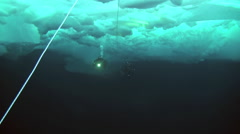 Diver under Arctic ice at the North Pole light the way a flashlight. Stock Footage