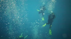 Scuba divers submerged in pool with many bubbles in deep pool Stock Footage