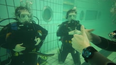 Girl and woman in wetsuits underwater and hands of instructor gesture Stock Footage
