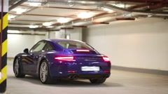 Blue sports car with burning rear lights in underground parking Stock Footage
