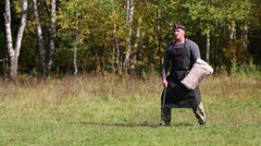 Men is dog trainer with whip and protection on hand teach doberman Stock Footage