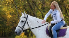 Woman with white hair sits on white horse and smiles Stock Footage