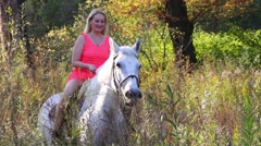 Woman in short pink dress riding on beautiful white horse outdoor Stock Footage