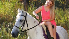 Woman in short pink dress sits sideways on white horse and strokes Stock Footage