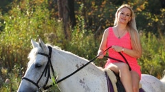 Woman in short pink dress sits sideways on white horse Stock Footage