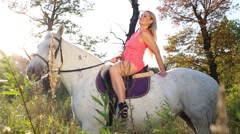 Woman in short pink dress sits arching up on white horse and rides Stock Footage
