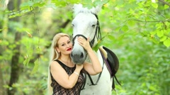 Woman in nature with white hair hugs head of white horse Stock Footage