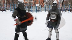 Three men dressed in medieval armor warm up before fight Stock Footage