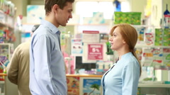 Pharmacist woman offers the visitor a cure at the chemists shop - stock footage