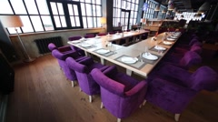 Tables with glasses and saucers and purple armchairs in restaurant Stock Footage