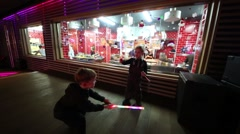 Children play with toy light swords near kitchen Stock Footage