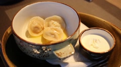 Bowl with three dumplings and small bowl with sour cream Stock Footage