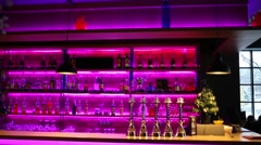 Bar with purple neon lights, hookahs and lots of bottles of alcohol Stock Footage