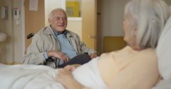 4K Happy senior couple in hospital room, man in wheelchair visiting sick wife Stock Footage