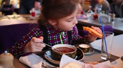 Cute little girl in colored shirt eats red-beet soup with bread Stock Footage