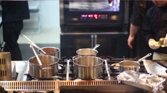 Five pots on stove in kitchen in cafe and cook in black clothing Stock Footage