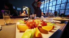 Girl taking slice of orange with plate of fruit on table Stock Footage