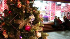 Christmas tree with decorations and people out of focus indoor Stock Footage