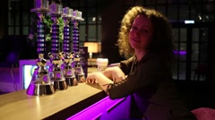 Beautiful woman with curly hair sitting at bar with neon lights Stock Footage