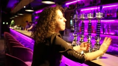Beautiful smiling woman with curly hair sings in bar with neon lights Stock Footage