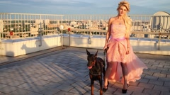 Beautiful blonde woman holding leash with Doberman on roof Stock Footage