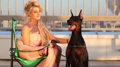 Beautiful blonde woman sits on folding chair and strokes Doberman Stock Footage