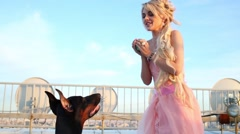 Beautiful blonde woman in pink dress with Doberman on roof Stock Footage