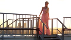 Beautiful blonde woman in pink dress on roof of tall building Stock Footage