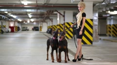 Beautiful blonde woman lets two Dobermans in underground parking Stock Footage