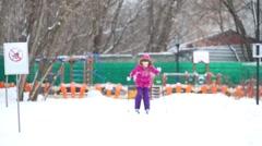 Girl child skiing during snowfall near children playground Stock Footage