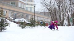 Girl child stands up after fall on ski during snowfall Stock Footage