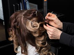 Master stylist makes the bride wedding styling. beautiful satisfied client in - stock photo