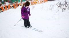 Girl skis during snowfall near children playground Stock Footage