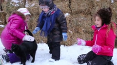 Three children and black cat on snow next to molded hay Stock Footage