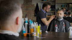 Barber trimming beard to his client. The vintage salon, master serving man. Gray Stock Footage