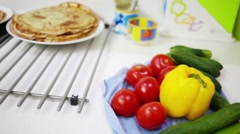 Bright fresh vegetables, pancakes on table and stove in kitchen Stock Footage
