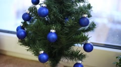 Small decorative Christmas tree with blue balls on windowsill Stock Footage