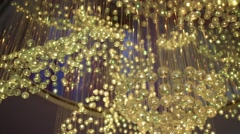 Glass balls hanging from chandeliers shimmering yellow, green, and blue Stock Footage