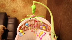 Closeup of small empty cot with attached toys in room Stock Footage