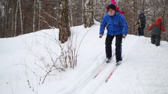 Man slides down from snow hill in woods next to three children skiers - stock footage