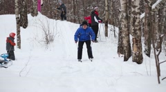 Man slides on skis from hill next to two adults and three children Stock Footage