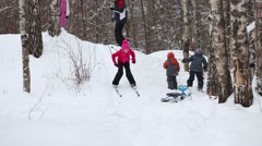 Girl slides on skis from hill next to two adults and two children on winter day Stock Footage
