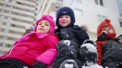 Close up of three children sitting on pile of snow. Stock Footage