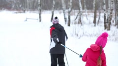 One adult and three children go skiing in chain on winter snowy day Stock Footage