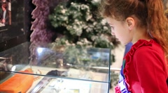 Serious girl looking at exhibits under glass in museum Stock Footage