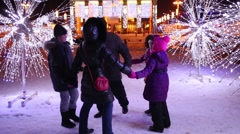 Five adults and children round dance on winter evening Stock Footage